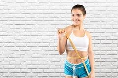 Mujer deportiva con la cinta métrica Fotografía de archivo