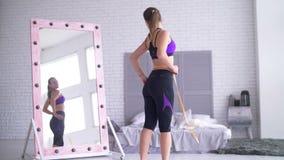 Mujer deportiva con la cinta métrica que mira el espejo metrajes