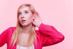 Mujer deportiva con la mano al oído que escucha Foto de archivo