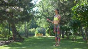 Mujer deportiva con las pesas de gimnasia que doblan los músculos al aire libre metrajes
