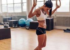 Mujer deportiva con los anillos del gimnasta en el gimnasio Imagenes de archivo