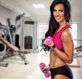 Mujer deportiva con pesas de gimnasia en gimnasio Imagen de archivo