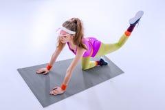 Mujer deportiva concentrada que ejercita en la estera del entrenamiento Imagen de archivo