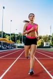 Mujer deportiva de la aptitud que activa en pista corriente roja en estadio Verano del entrenamiento al aire libre en línea corri Foto de archivo libre de regalías