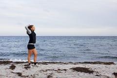 Mujer deportiva de la aptitud que se coloca en la playa después de entrenamiento Imagenes de archivo