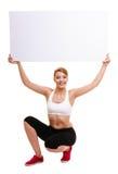Mujer deportiva de la aptitud que sostiene la bandera vacía en blanco del anuncio Foto de archivo