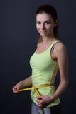 Mujer deportiva delgada hermosa con la cinta de la medida sobre gris Imagenes de archivo