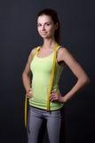 Mujer deportiva delgada hermosa joven con la cinta de la medida sobre gris Imágenes de archivo libres de regalías