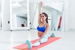 Mujer deportiva en el sujetador de los deportes que hace el ejercicio partido del frente que estira sus piernas Imagen de archivo libre de regalías