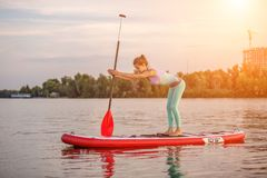 Mujer deportiva en la posición de la yoga respecto al paddleboard, haciendo yoga en tablero del sorbo, el ejercicio para la flexi fotos de archivo libres de regalías