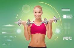 Mujer deportiva feliz con las pesas de gimnasia que doblan bíceps Imagen de archivo libre de regalías