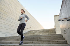 Mujer deportiva feliz que corre abajo en ciudad Imágenes de archivo libres de regalías
