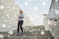 Mujer deportiva feliz que corre abajo en ciudad Foto de archivo