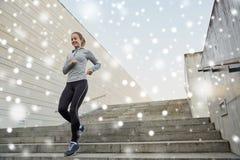 Mujer deportiva feliz que corre abajo en ciudad Foto de archivo libre de regalías