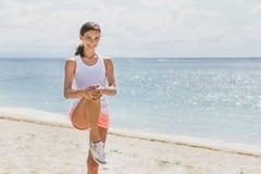 Mujer deportiva feliz que hace las piernas que estiran antes de activar imágenes de archivo libres de regalías