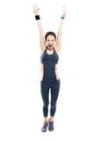 Mujer deportiva feliz que se coloca con las manos aumentadas para arriba Foto de archivo libre de regalías