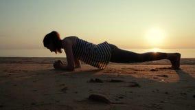 Mujer deportiva hermosa en la posición del tablón respecto a la playa durante puesta del sol metrajes