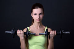 Mujer deportiva hermosa joven con pesas de gimnasia sobre gris Foto de archivo libre de regalías