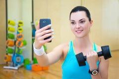 Mujer deportiva hermosa que hace la foto del selfie con pesa de gimnasia en smar Imágenes de archivo libres de regalías