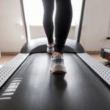Mujer deportiva joven atractiva que se resuelve en el gimnasio La muchacha está haciendo el entrenamiento cardiio en la rueda de  fotografía de archivo