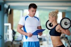 Mujer deportiva joven con el levantamiento de pesas del ejercicio del instructor Imagen de archivo