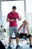 Mujer deportiva joven con el levantamiento de pesas del ejercicio del instructor Foto de archivo