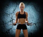 Mujer deportiva joven con las pesas de gimnasia que doblan bíceps Imagen de archivo libre de regalías
