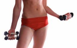 Mujer deportiva joven con pesa de gimnasia Fotos de archivo