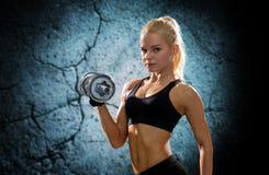 Mujer deportiva joven con pesa de gimnasia de acero pesada Foto de archivo