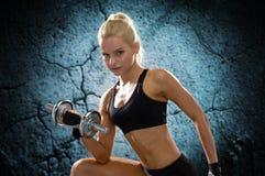 Mujer deportiva joven con pesa de gimnasia de acero pesada Fotografía de archivo