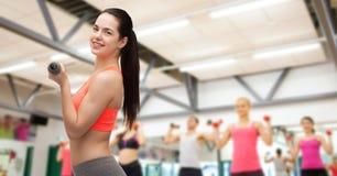Mujer deportiva joven con pesas de gimnasia ligeras Fotos de archivo libres de regalías