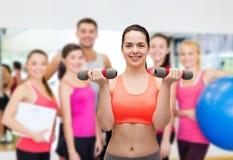 Mujer deportiva joven con pesas de gimnasia ligeras Foto de archivo