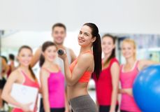 Mujer deportiva joven con pesas de gimnasia ligeras Fotos de archivo