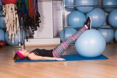 Mujer deportiva joven en el gimnasio que hace exercice de la aptitud con la bola azul Foto de archivo libre de regalías