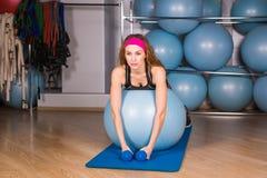 Mujer deportiva joven en el gimnasio que hace exercice de la aptitud con la bola azul Fotos de archivo libres de regalías