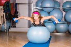 Mujer deportiva joven en el gimnasio que hace exercice de la aptitud con la bola azul Imágenes de archivo libres de regalías