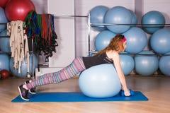 Mujer deportiva joven en el gimnasio que hace exercice de la aptitud con la bola azul Fotografía de archivo