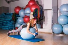 Mujer deportiva joven en el gimnasio que hace exercice de la aptitud con la bola azul Imagenes de archivo