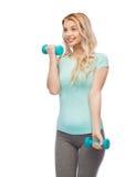 Mujer deportiva joven hermosa feliz con pesas de gimnasia Imágenes de archivo libres de regalías