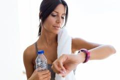 Mujer deportiva joven hermosa que mira su smartwatch en casa Fotografía de archivo libre de regalías