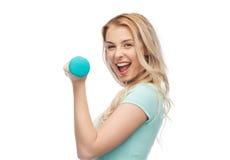 Mujer deportiva joven hermosa sonriente con pesa de gimnasia Fotografía de archivo