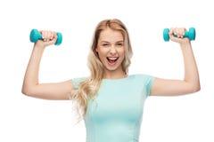 Mujer deportiva joven hermosa sonriente con pesa de gimnasia Fotos de archivo libres de regalías