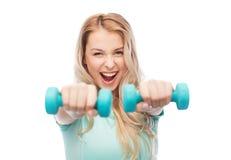 Mujer deportiva joven hermosa sonriente con pesa de gimnasia Foto de archivo libre de regalías