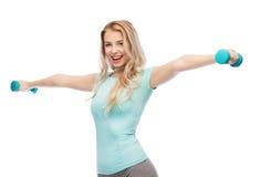 Mujer deportiva joven hermosa sonriente con pesa de gimnasia Imagen de archivo libre de regalías