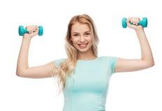 Mujer deportiva joven hermosa sonriente con pesa de gimnasia Foto de archivo