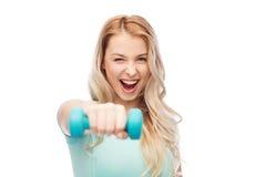 Mujer deportiva joven hermosa sonriente con pesa de gimnasia Imagenes de archivo
