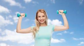 Mujer deportiva joven hermosa sonriente con pesa de gimnasia Imagen de archivo
