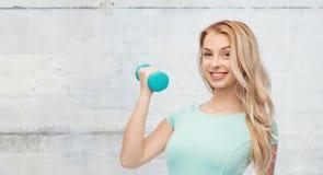 Mujer deportiva joven hermosa sonriente con pesa de gimnasia Imágenes de archivo libres de regalías