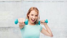 Mujer deportiva joven hermosa sonriente con pesa de gimnasia Fotografía de archivo libre de regalías