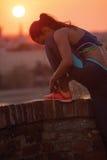 Mujer deportiva joven que ata cordones foto de archivo